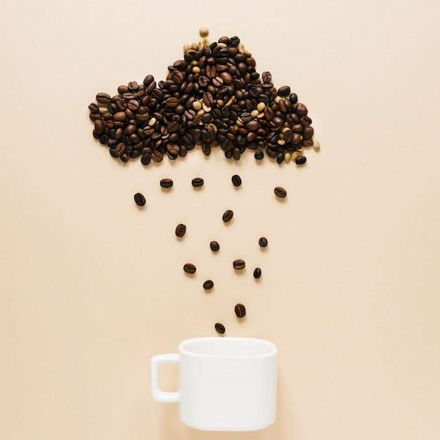 Coupe avec nuage de grains de café Photo gratuit