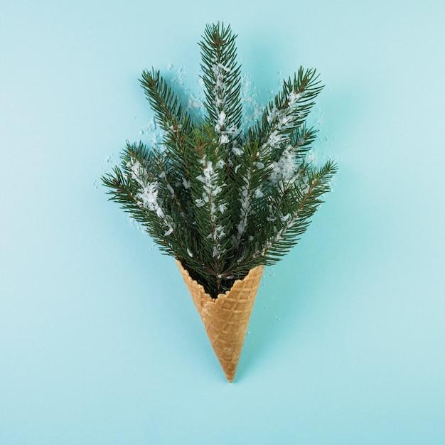 Coupe de plaquette avec brindille de sapin et neige d'ornement Photo gratuit