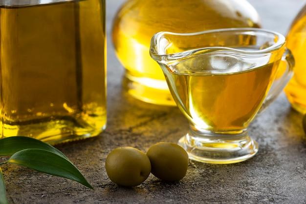Coupe près de l'huile d'olive et des olives vertes Photo gratuit