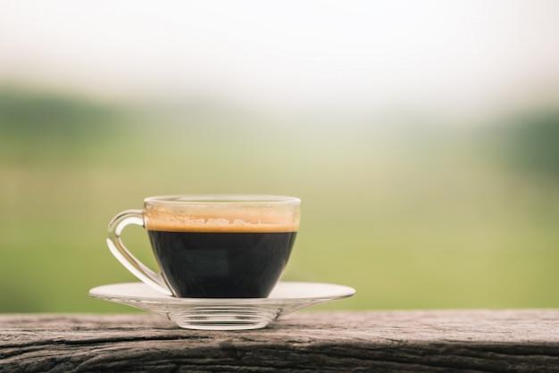 Coupe en verre café chaud sur une table en bois dans un café avec fond naturel vert. Photo Premium
