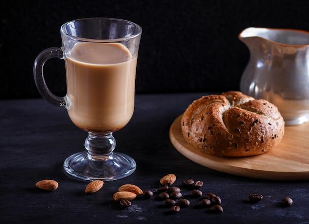 Coupe en verre de café avec de la crème et un pain sur une table noire. Photo Premium