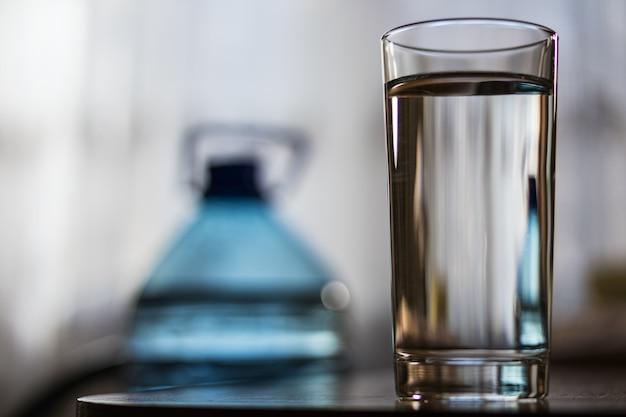 Coupe en verre avec de l'eau et une bouteille en plastique Photo Premium