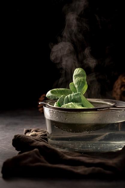 Coupe en verre avec un filet de thé et des feuilles de thé Photo gratuit