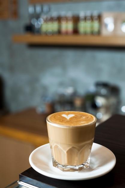 Coupe en verre de latte avec art au latte à la cafétéria Photo gratuit