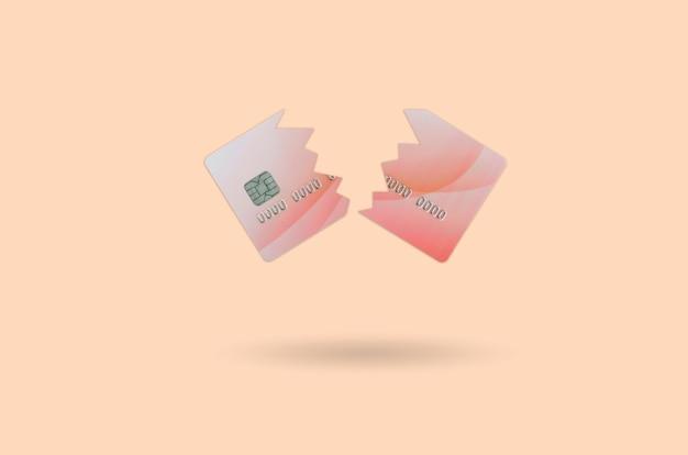 Couper la carte de crédit rouge cassée isolée sur orange Photo Premium