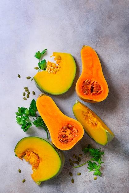 Couper La Citrouille Orange Mûre Avec Des Graines Et Des Herbes En Gris Clair. Concept D'aliments Biologiques Sains Végétariens Et Crus, Régime Alimentaire. Photo Premium