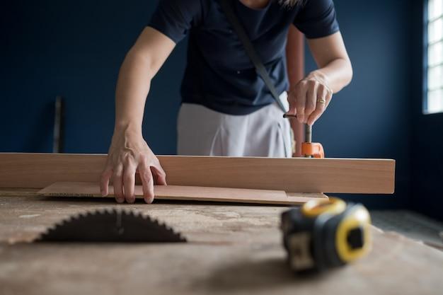 Couper du bois pour la construction, perceuse à bois, charpentier, ouvrier Photo Premium