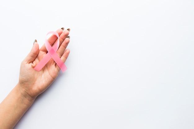 Couper la main avec un ruban rose Photo gratuit