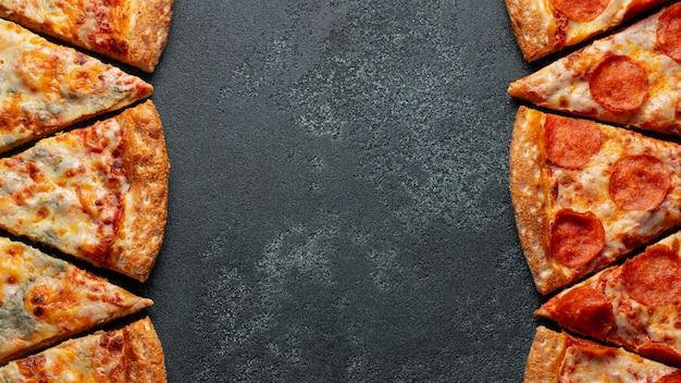 Couper en tranches de délicieux pepperoni à la pizza fraîche et une pizza four cheese sur un fond sombre. Photo Premium