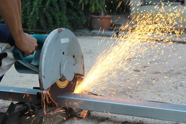 Couper un tuyau en métal avec des éclaboussures d'étincelles. Photo Premium