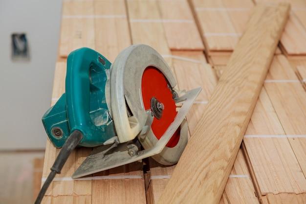Couper le vieux parquet avec une scie électrique Photo Premium
