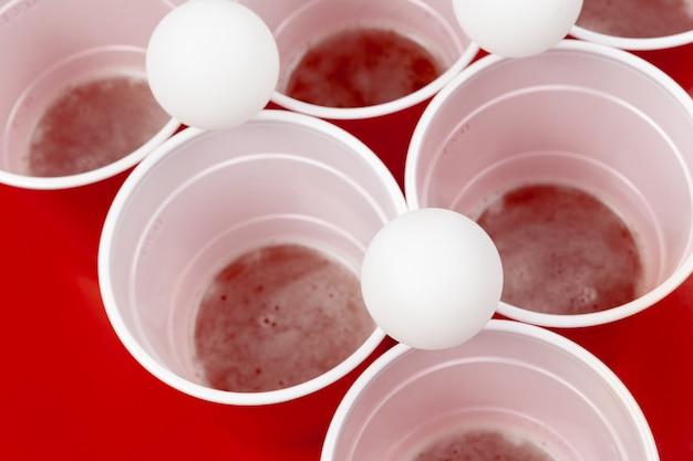 Coupes et boule en plastique. jeu de bière pong Photo Premium