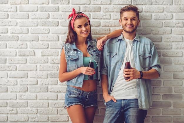 Couple d'adolescents élégant tenant une bouteille d'eau gazeuse. Photo Premium