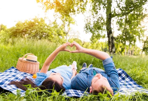 Couple adulte multiracial faisant signe de coeur avec les doigts Photo gratuit