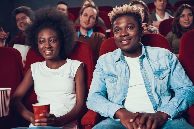 Couple africain avec pop-corn en regardant un film au cinéma Photo Premium