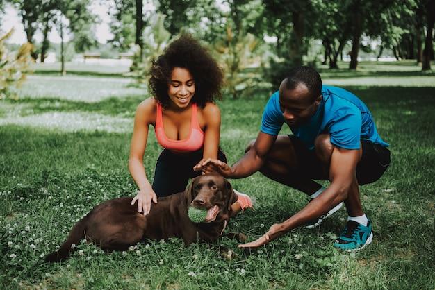 Couple afro-américain dans sportswear petting dog. Photo Premium