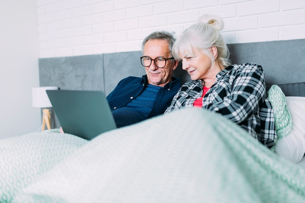 Couple âgé au lit avec un ordinateur portable Photo gratuit
