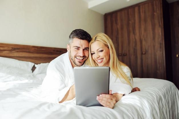 Un Couple D'âge Moyen Amoureux à L'aide D'une Tablette Allongé Sur Le Lit En Lune De Miel. Intérieur D'appartement D'hôtel. Photo Premium