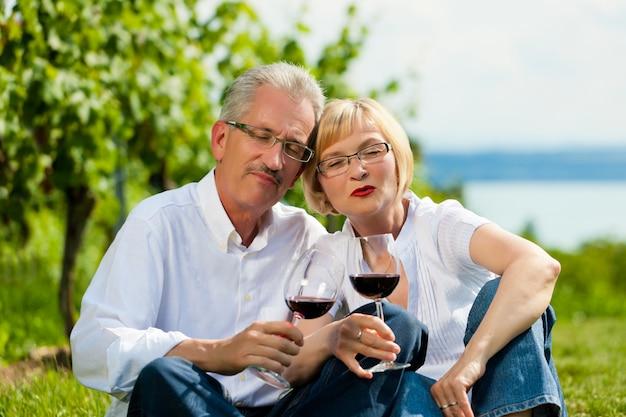 Couple d'âge mûr boire du vin dans la nature Photo Premium