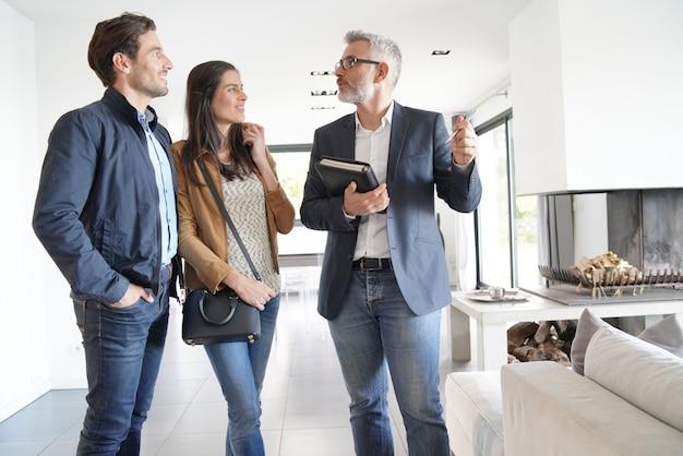 Couple avec agent immobilier visitant une maison moderne Photo Premium