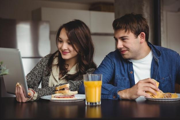 Couple à L'aide De Tablette Numérique Tout En Prenant Le Petit Déjeuner Photo gratuit
