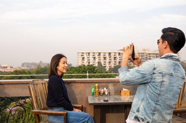 Couple à l'aide de téléphone portable, prenant des photos de l'autre au café en plein air. Photo Premium