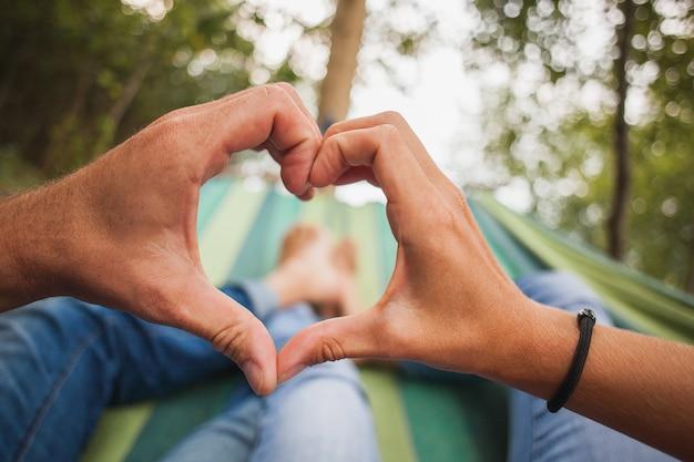 Couple Allongé Dans Un Hamac Faisant Le Symbole Du Coeur Photo gratuit