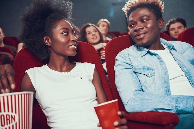 Couple américain avec pop-corn en regardant un film au cinéma. Photo Premium