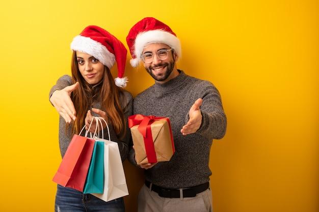 Couple Ou Amis Tenant Des Cadeaux Et Des Sacs à Provisions Tendre La Main Pour Saluer Quelqu'un Photo Premium