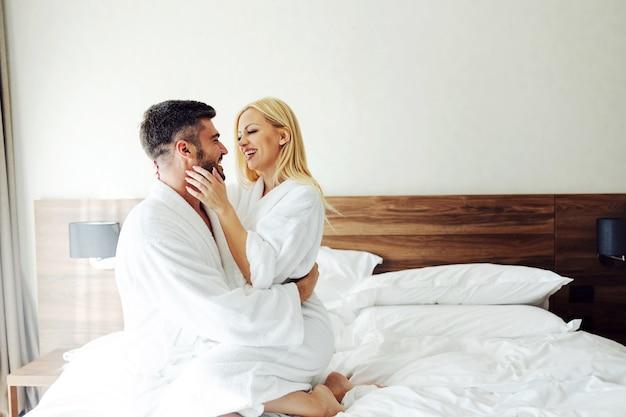 Un Couple Amoureux D'âge Moyen Assis Sur Le Lit D'un Hôtel, Câlins Et Célébrant Son Anniversaire. Photo Premium