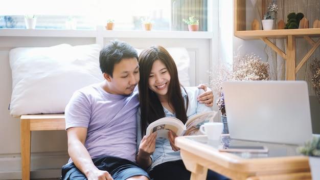 Couple d'amoureux asiatique assis et lisant un livre le matin avec une sensation de chaleur Photo Premium
