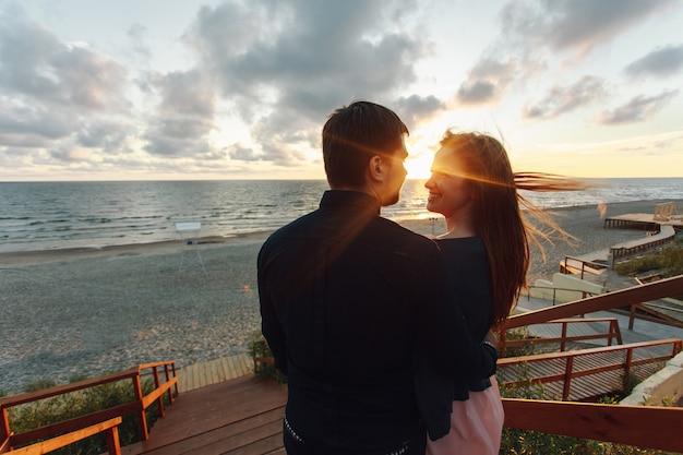 Couple d'amoureux au premier rendez-vous à l'heure du coucher de soleil à la mer Photo Premium