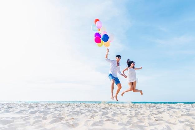 Couple d'amoureux de bonheur tenant des ballons colorés et sauter sur la plage en journée ensoleillée Photo Premium
