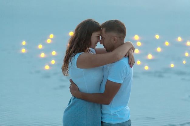 Couple amoureux calins romantiques dans le désert de sable. soirée, ambiance romantique, bougies brûlées dans le sable Photo Premium