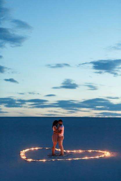 Couple amoureux calins romantiques dans le désert de sable. soirée, ambiance romantique, dans le sable, brûle des bougies en forme de coeur Photo Premium