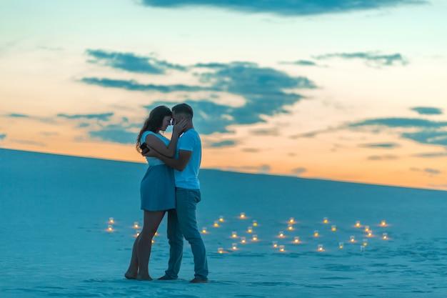 Couple Amoureux Calins Romantiques Dans Le Désert De Sable, Soirée, Atmosphère Romantique, Dans Le Sable, Brûler Des Bougies Photo Premium