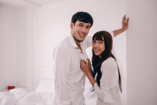 Couple amoureux couché sur la chambre bonheur lifestyle et fille souriante se détendant dans un lit blanc Photo Premium