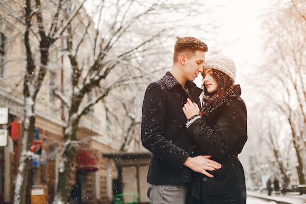 Couple D'amoureux élégant En Manteaux Noirs Marchant Dans La Ville De Neige D'hiver Photo Premium