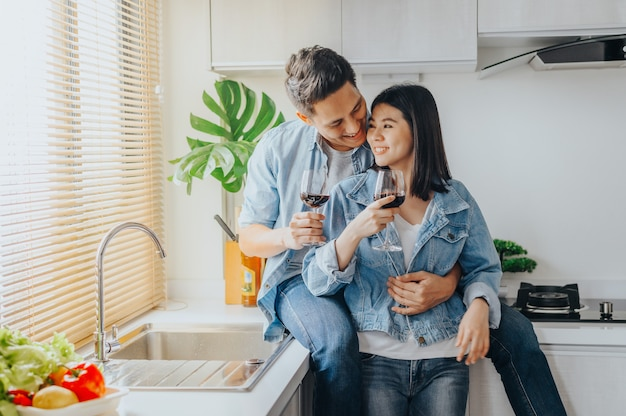Couple amoureux embrassant et buvant du vin rouge dans la cuisine Photo Premium