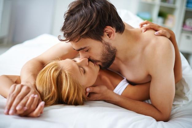 Couple amoureux embrassant dans le lit Photo gratuit