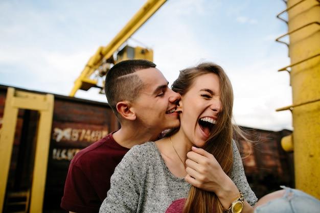 Couple amoureux. jeune homme mordillant ludiquement l'oreille de la petite amie. histoire d'amour. Photo gratuit