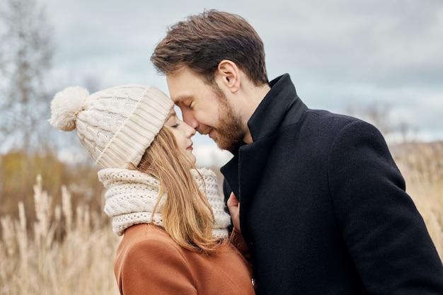Couple D'amoureux Marchant Dans Le Parc En Automne Câlins Et Bisous. Photo Premium