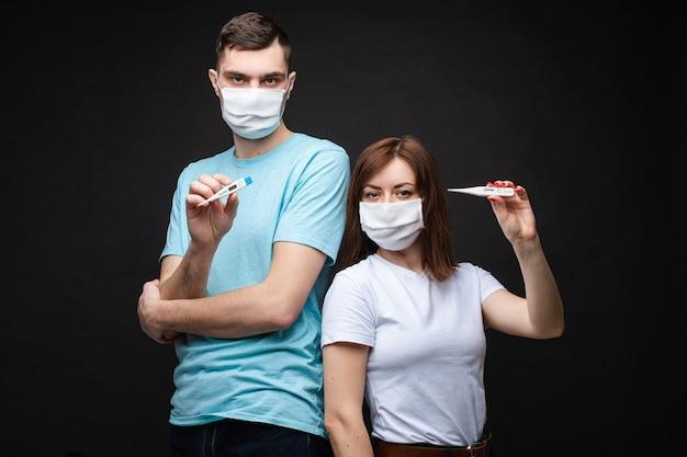 Couple Amoureux En Masques Médicaux Blancs Ont Peur Du Coronavirus Et Montre Des Thermomètres Photo Premium