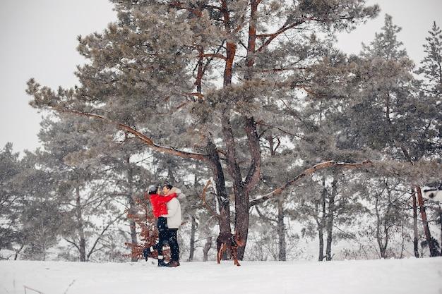 Couple d'amoureux à pied dans un parc d'hiver Photo gratuit