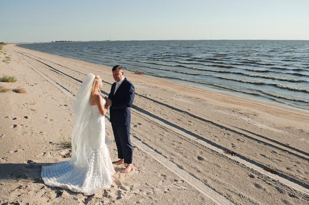 Couple Amoureux Sur La Plage Le Jour De Leur Mariage. Photo Premium