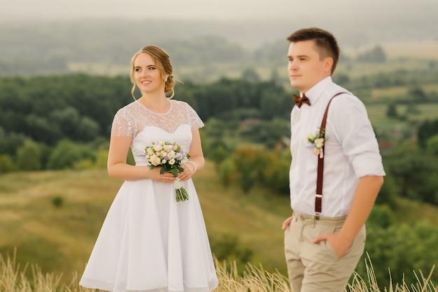 Un Couple D'amoureux Posant Contre Une Belle Vue. Jour De Mariage. Jeunes Mariés. Photo Premium
