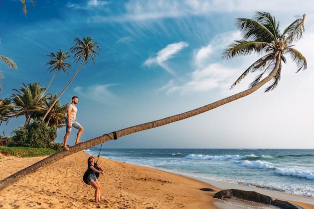 Un couple amoureux rencontre le coucher de soleil sur la plage avec des palmiers. voyage de mariage. homme et femme voyageant en asie. homme et femme au repos au sri lanka. couple amoureux au coucher du soleil couple sur l'île Photo Premium