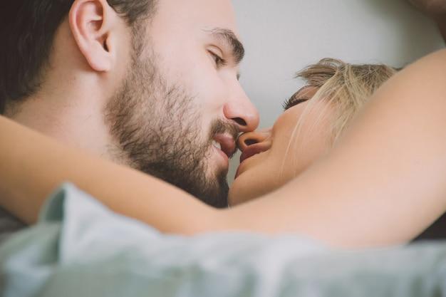 Couple d'amoureux s'embrassant au lit Photo Premium