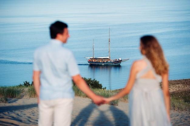 Un Couple Amoureux Se Dresse Sur La Plage Dans Les Dunes Dans Le Contexte De La Mer Baltique Et D'un Navire Photo Premium