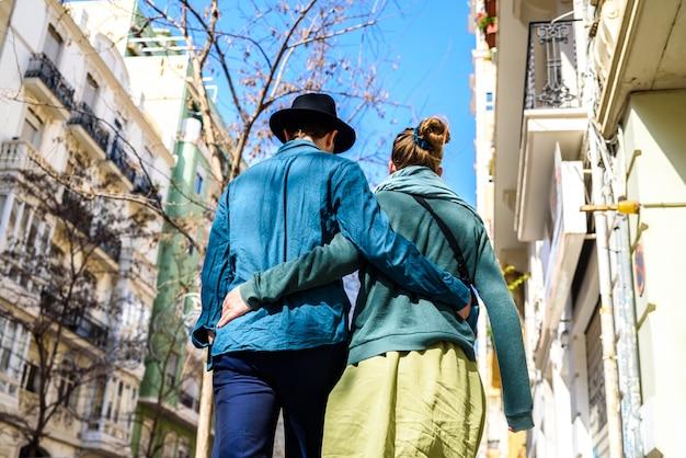 Un couple d'amoureux se promenant dans les rues alors que les touristes, habillés dans un style élégant et décontracté, s'embrassaient. Photo Premium